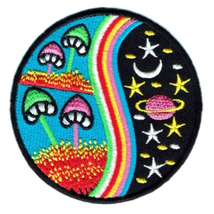 Round embroidered patch featuring mushrooms stars and planets.