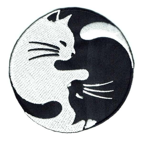 Round iron on embroidered patch of a black and white cat in yin yang pose