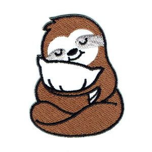 Iron on brown sloth patch cuddling a white pillow.
